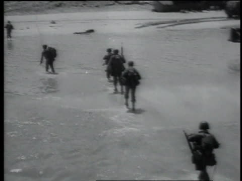 soldiers walk through water to shore bulldozer is driven onto land / normandy france - normandie stock-videos und b-roll-filmmaterial