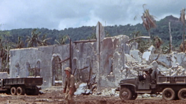 soldiers walking by building wreckage and parked m35 trucks / guam mariana islands - guam stock videos & royalty-free footage