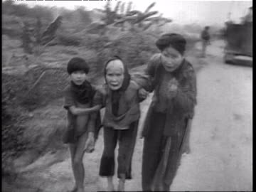 soldiers walking on path thru field with fire in background during vietnam war / three scared and hungry vietnamese refugees walking from field to... - civilian stock videos & royalty-free footage