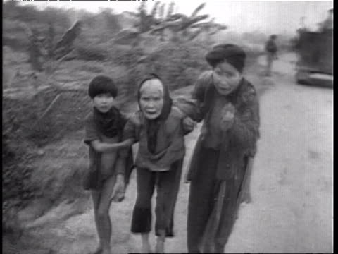soldiers walking on path thru field with fire in background during vietnam war / three scared and hungry vietnamese refugees walking from field to... - 1965 stock videos & royalty-free footage