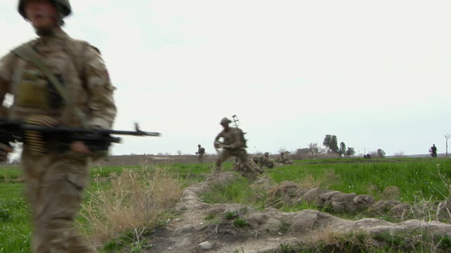 soldiers walking through landscape / mausa qala, helmand province, afghanistan. - forze armate britanniche video stock e b–roll