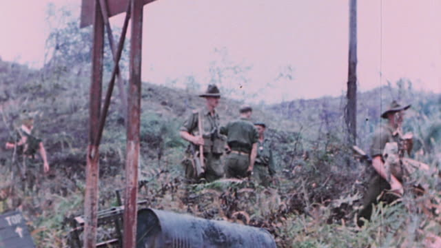 soldiers walking with rifles on their shoulders, and u.s. army soldier smoking a cigarette, carrying camera, and listening on hand-held radio / the... - anzac day stock videos & royalty-free footage