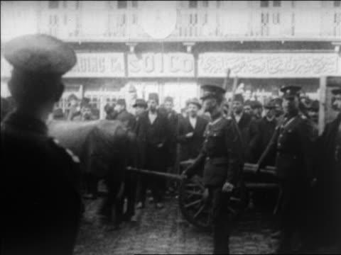 B/W 1920 soldiers watch as horse pulls cart thru crowd / Turkey / newsreel