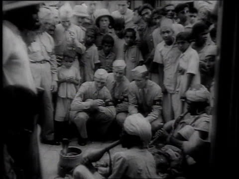 stockvideo's en b-roll-footage met montage soldiers watching a snake charmer on a city street / india - charmant