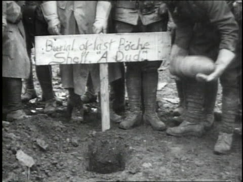 soldiers watching as soldier lowers shell into grave and buries it, standing in front of sign that reads 'burial of last boche shell. a dud.' / - 1918 stock videos & royalty-free footage