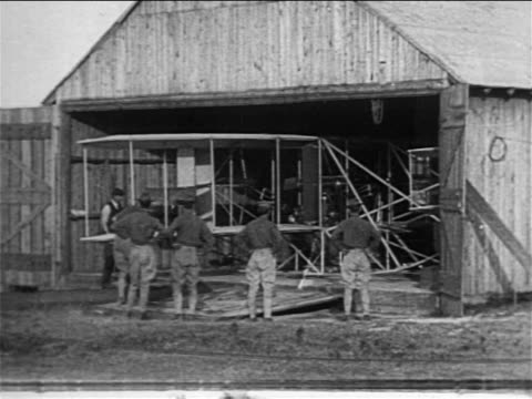 b/w 1908 soldiers watching as wright brothers' airplane is removed from barn / documentary - wright flyer stock-videos und b-roll-filmmaterial