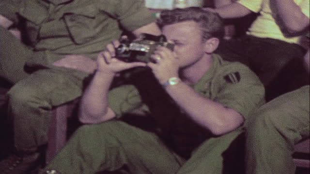 soldiers watching performance of rock and roll band and dancer from audience / da nang vietnam - ダナン点の映像素材/bロール