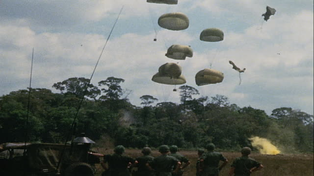 vídeos de stock, filmes e b-roll de soldiers watching supply airdrop parachutes drifting down and parachute silk draped across trees / vietnam - formato letterbox