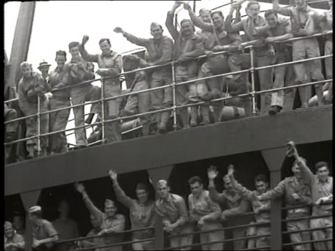 Soldiers wave from the deck of a ship