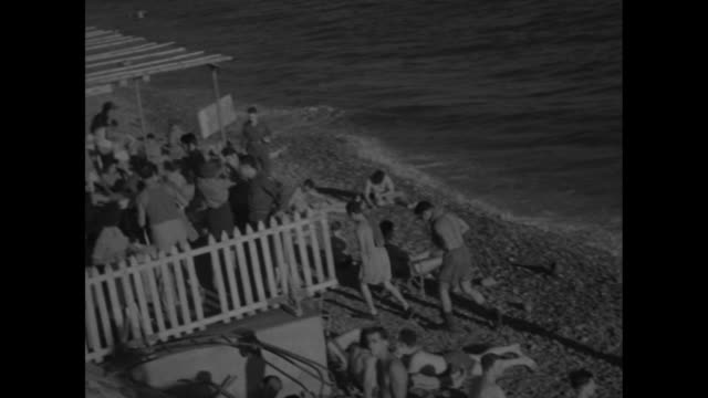 us soldiers wearing bathing trunks sit walk mingle on the beach at the french riviera as waves lap onto shore / driveby shot row of elaborate hotels... - paddle boat stock videos & royalty-free footage