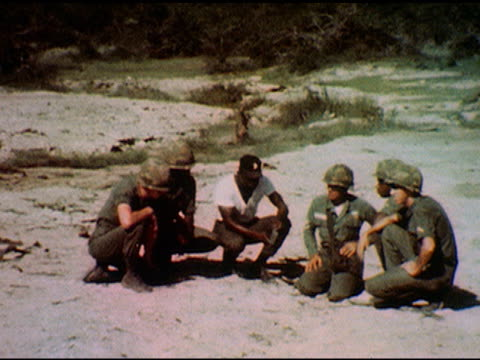 / soldiers wearing helmets crouch near ground, officer directs them to set up a mine / soldier lying on ground sets aim for mine / soldier attaches... - barricade stock videos & royalty-free footage