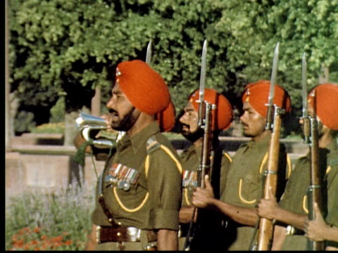 1960 montage soldiers wearing olive colored uniforms and red turbans march in formation with rifles in front of large mosque / india - 軍事点の映像素材/bロール