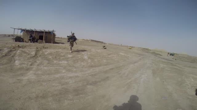 soldiers with 4th squadron 2d cavalry regiment patrol through a village on march 9, 2014 near kandahar, afghanistan. - infanteri bildbanksvideor och videomaterial från bakom kulisserna