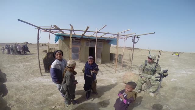 stockvideo's en b-roll-footage met soldiers with 4th squadron 2d cavalry regiment patrol through a village on march 9 2014 near kandahar afghanistan - kandahar afghanistan