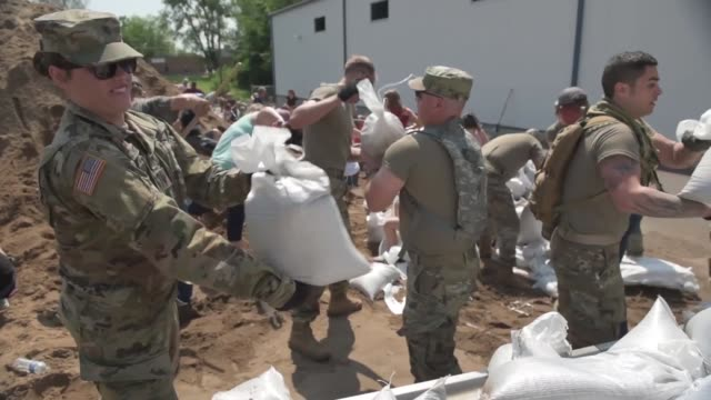 soldiers with illinois national guard assist volunteers and members of the community to fill and load sandbags in qunincy illinois in response to... - prevention stock videos & royalty-free footage
