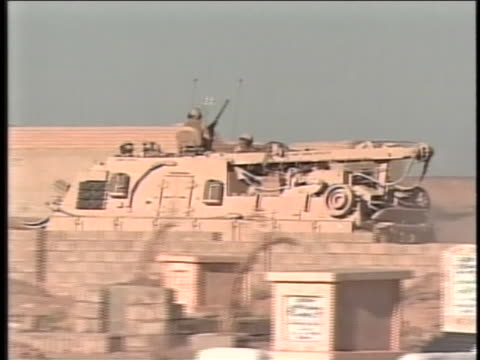 soldiers with large guns ride atop a tank as it drives. - al fallujah stock videos & royalty-free footage