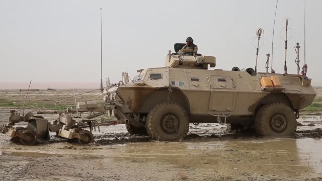 vídeos de stock e filmes b-roll de soldiers with the afghan national army recover a tactical vehicle after it becomes stuck in a muddy field while on patrol with soldiers from the us... - kandahar