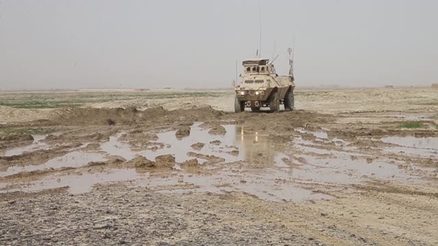 soldiers with the afghan national army travel through a muddy field while on patrol with soldiers from the u.s. army's 4th squadron 2d cavalry... - afghan national army stock videos & royalty-free footage