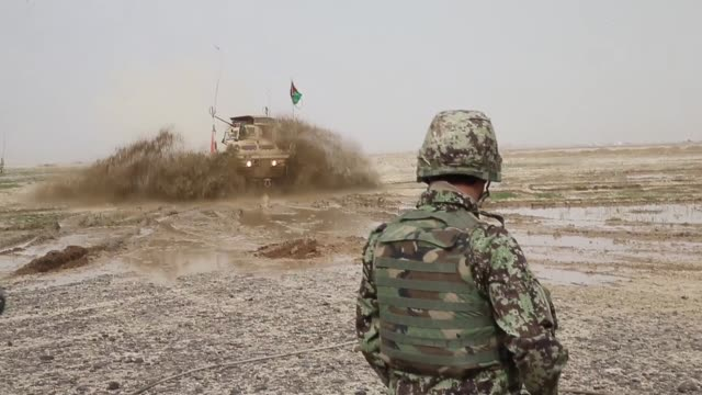 vídeos de stock e filmes b-roll de soldiers with the afghan national army travel through a muddy field while on patrol with soldiers from the us army's 4th squadron 2d cavalry regiment... - kandahar
