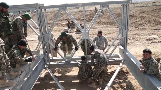 soldiers with the afghan national army's national engineer brigade learn how to construct a mabey-johnson portable pre-fabricated bridge with the... - afghan national army stock videos & royalty-free footage