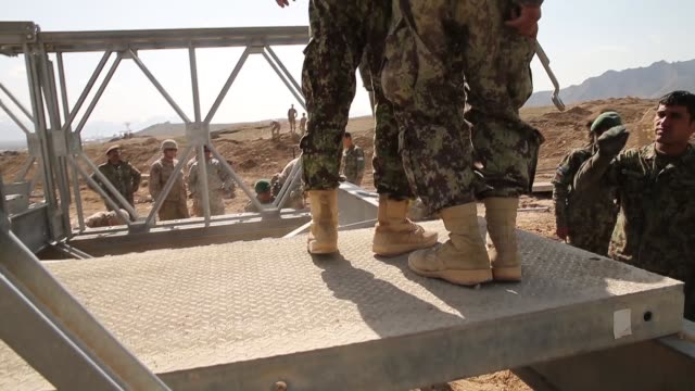 CU Soldiers with the Afghan National Army's National Engineer Brigade learn how to construct a MabeyJohnson portable prefabricated bridge with the...