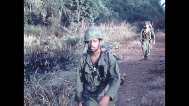 soldiers with weapons and rucksacks enter from right and move along a road exiting to the left last soldier gives the peace sign to the camera - vietnamkrieg stock-videos und b-roll-filmmaterial