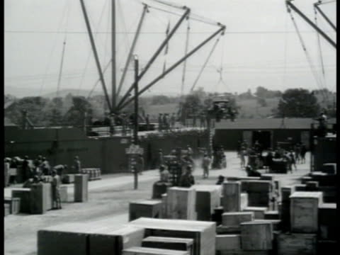 soldiers working in open area depot w/ stacked boxes truck being moved w/ crane us soldiers working wench crane cable lowering supply boxes to... - lowering stock videos & royalty-free footage