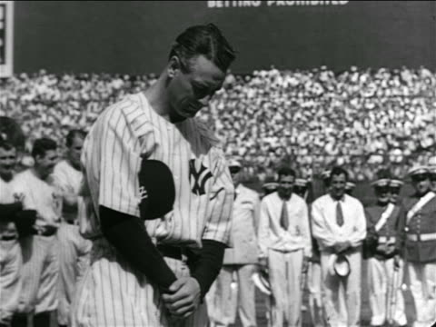 B/W 1939 solemn Lou Gehrig chewing gum looking down then looking up in crowded stadium / farewell