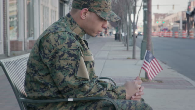 solemn military man holds an american flag - young war veteran stock videos & royalty-free footage