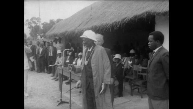Solemn small crowd watches as the newest chief of the Guto Tribe is sworn in in Fort Victoria Rhodesia / white man places overcoat on new 70 year old...