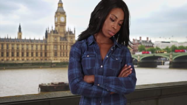 solitary black woman stands sullenly in london near big ben by river thames - big ben点の映像素材/bロール