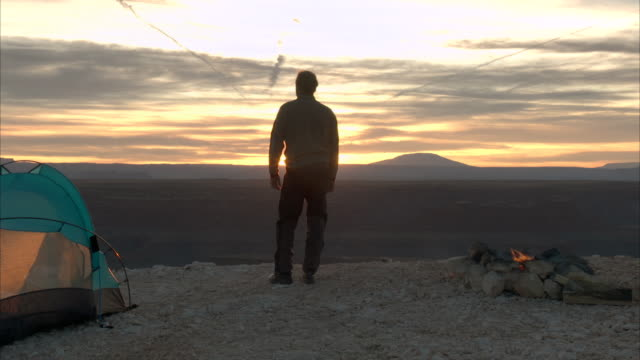 a solitary camper admires the desert view near his tent. - campeggiare video stock e b–roll