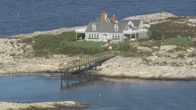 aerial solitary cape cod house with dormers, veranda, and private jetty on tiny island / new hampshire, united states - dacherker stock-videos und b-roll-filmmaterial