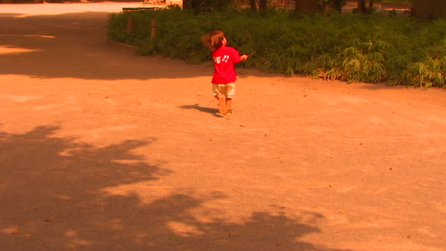 WS PAN Solitary child running through public park to play area, Tokyo, Japan