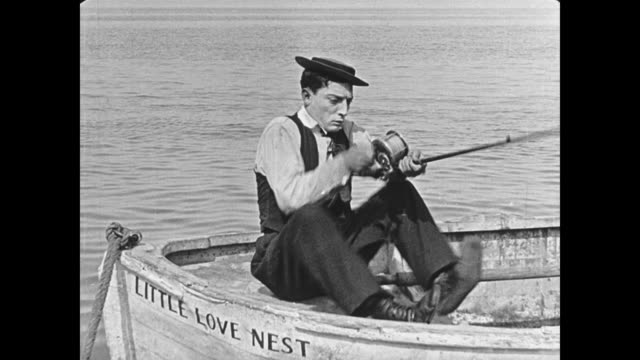 vídeos de stock, filmes e b-roll de 1923 solitary man (buster keaton) on ocean fishes, shoots hole in boat then struggles to stay above water - 1923