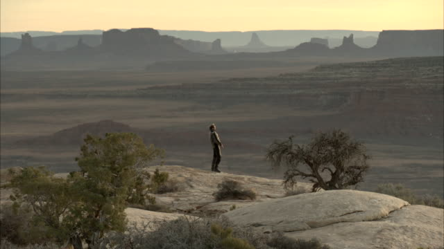 A solitary man shouts from the top of a rock with a sweeping desert vista.