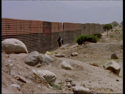 Solitary man walks along border fence Mexico