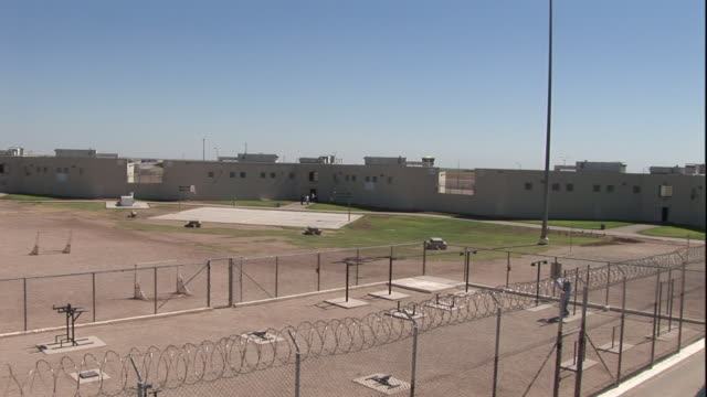 a solitary prisoner performs pull-ups in a large prison yard and then walks around. - bodyweight training stock videos & royalty-free footage