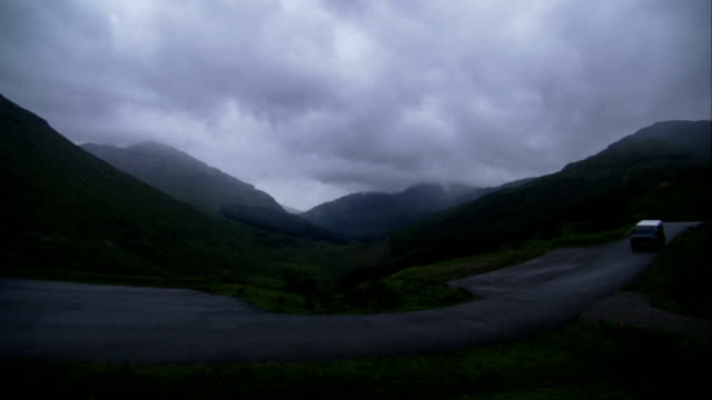 A solitary SUV drives along a road in the Scottish higlands. Available in HD.