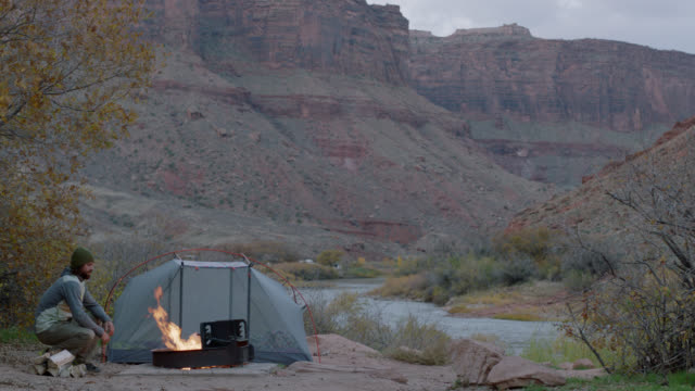 solitary young man sits by fire pit at scenic moab camp site. - camping stock videos & royalty-free footage