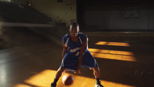 A basketball player practice his ball-handling skills in front of empty bleachers.