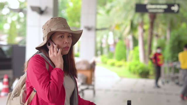 solo beautiful asian woman, a traveler with long black hair, hat, shoulder bag, and luggage on pushcart waiting on the airport, talking friend on a smartphone at a terminal, looking taxi, transportation to explore the new journey. - shoulder bag stock videos & royalty-free footage