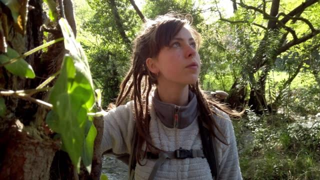 vidéos et rushes de randonneur féminin solitaire restant dans la forêt - seulement des jeunes femmes