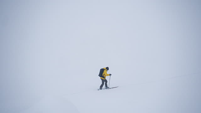 solo man splitboarding across fresh snow - powder snow stock videos & royalty-free footage