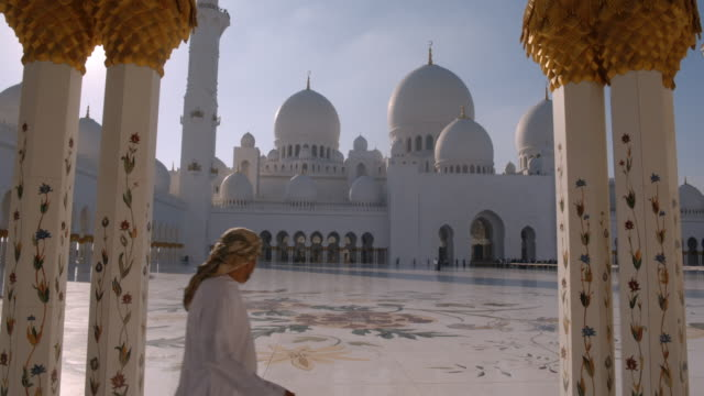 solo man walks in grand mosque, abu dhabi - oberkörperaufnahme stock-videos und b-roll-filmmaterial