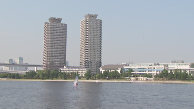 solo person parasailing on the water in front of buildings in tokyo, japan. - sport点の映像素材/bロール
