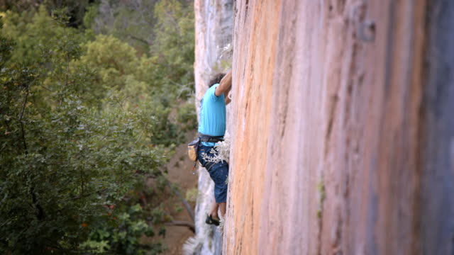 solo rock climber ascends sheer rock face - olympos, turkye - rock face stock videos & royalty-free footage