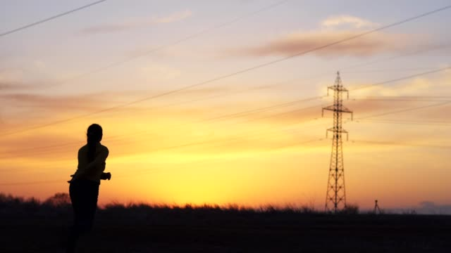 Solo Traveler at Sunset Having Fun, Dancing, One Young Woman Tourist Outdoors, Happiness, Enjoying the Sunset Light, Portrait, Back Lit, Travel, Exploration, Adventure, Tourism, Nature, Electricity, Electricity Pylon,