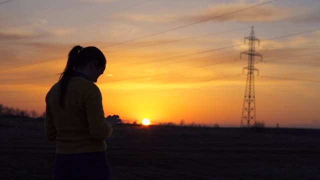 Solo Traveler at Sunset Using Smartphone, Taking Pictures, One Young Woman Tourist Using Internet, Chatting, Enjoying the Sunset Light, Portrait, Back Lit, Travel, Exploration, Adventure, Tourism, Outdoors, Mountain Hiking, Electricity, Energetics,