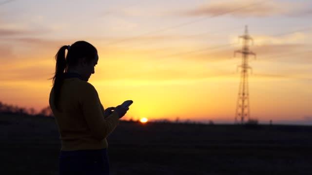 vidéos et rushes de voyageur solo au coucher du soleil utilisant le smartphone, prenant des photos, une jeune femme touriste utilisant l'internet, bavardant, appréciant la lumière de coucher de soleil, portrait, arrière allumé, voyage, exploration, aventure, tourisme, à  - photo messaging